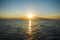 Por do sol sobre o oceano através das nuvens Imagem de Stock