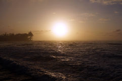 Por do sol sobre o oceano com as ondas que movem-se para a costa Fotografia de Stock