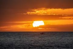 Por do sol sobre o oceano com o barco de pesca pequeno fotografia de stock royalty free