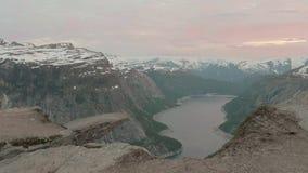 Por do sol sobre o Trolltunga Noruega, tiro liso da zorra video estoque