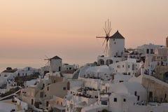 Por do sol sobre os moinhos de vento brancos na cidade de Oia e de panorama à ilha de Santorini, Thira, Grécia Imagens de Stock