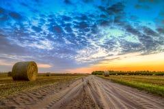 Por do sol sobre pacotes rurais da estrada e de feno Imagens de Stock