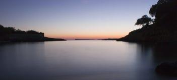 Por do sol sobre a praia de Cala Graccio Fotografia de Stock