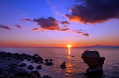 Por do sol sobre a praia rochosa foto de stock royalty free