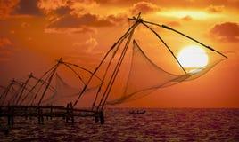 Por do sol sobre redes de pesca chinesas em Cochin Fotos de Stock