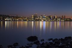 Por do sol sobre a skyline do ` s de Seattle que cria reflexões no lago Washington Imagem de Stock