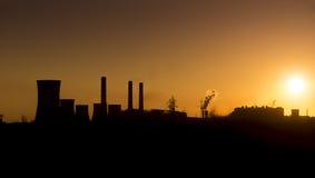Por do sol sobre sobre a fábrica da silhueta Fotografia de Stock Royalty Free