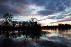 Por do sol sobre Tamisa inundada Fotos de Stock