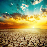 Por do sol sobre a terra da seca fotografia de stock