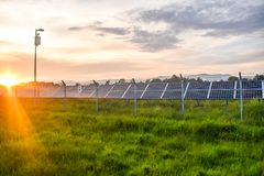 Por do sol sobre um central elétrica fotovoltaico com os módulos fotovoltaicos para a energia renovável no campo Gera??o das ener imagem de stock royalty free