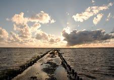 Por do sol sobre um quebra-mar perto de Tonder, Dinamarca Foto de Stock Royalty Free