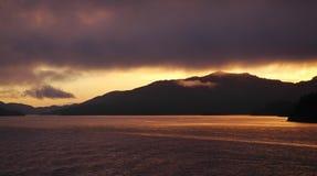 Por do sol sobre uma baía cercada por montanhas Fotos de Stock
