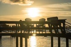 Por do sol sobre uma doca na praia imagem de stock