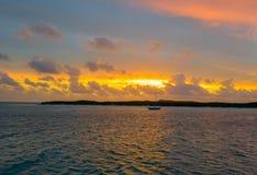 Por do sol sobre uma ilha no Bahamas e em uma navigação do barco de navigação no oceano foto de stock royalty free