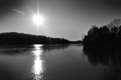 Por do sol sobre uma paisagem preto e branco do lago Foto de Stock