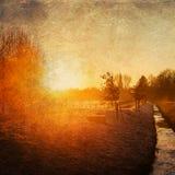 Por do sol sobre uma paisagem rural com textura do grunge fotografia de stock