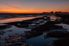 Por do sol sobre uma praia rochosa na parte dianteira os hotéis foto de stock