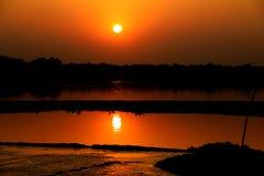Por do sol sobre a vila do rio imagens de stock royalty free