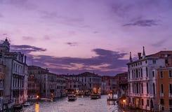 Por do sol surpreendente em Veneza sobre o canal grande com construções Venetian típicas, iluminando luzes e barcos Fotos de Stock Royalty Free