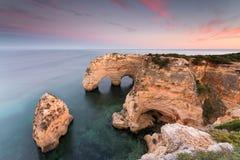Por do sol surpreendente na praia de Marinha no Algarve, Portugal Paisagem com cores fortes de um dos destinos principais do feri imagem de stock