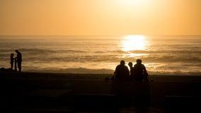 Por do sol vívido bonito da praia com os povos mostrados em silhueta sobre Oceano Atlântico em Vila do Conde, Porto, Portugal fotografia de stock royalty free