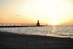 Por do sol do verão sobre o farol no Lago Michigan na cidade indiana de michigan imagens de stock