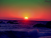 Por do sol verde e vermelho sobre o mar Fotos de Stock Royalty Free