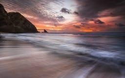 Por do sol vermelho após um dia nebuloso em uma praia isolada Imagens de Stock