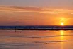 Por do sol vermelho com o Sillohettes em Long Beach fotografia de stock