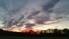 Por do sol vermelho no campo Imagens de Stock