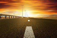 Por do sol vermelho sobre a estrada Fotos de Stock Royalty Free