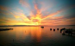 Por do sol vibrante na água, balsa que vem em casa Fotos de Stock