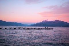 Por do sol violeta romântico em um lago com um cais e um pessoa longos wal imagens de stock