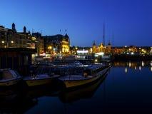 Por el anochecer Damrak, Amsterdam, Holanda Foto de archivo libre de regalías