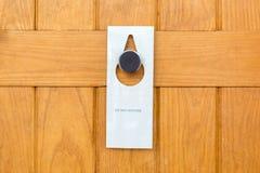 Por favor não perturbe o sinal na porta de madeira Closed da sala de hotel foto de stock