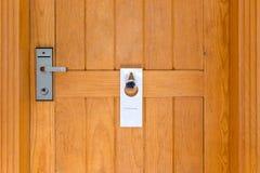 Por favor não perturbe o sinal na porta de madeira Closed da sala de hotel fotografia de stock royalty free