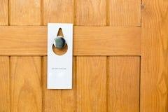 Por favor n?o perturbe o sinal na porta de madeira Closed da sala de hotel imagem de stock