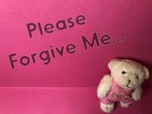 Por favor perdóneme la nota escrita sobre el fondo rosado con el oso de peluche triste lindo fotos de archivo