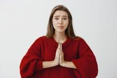 Por favor querido, quiero el anillo La hembra caucásica apuesta en el suéter flojo rojo, llevando a cabo las manos adentro ruega  foto de archivo