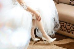 Por la mañana, la novia en medias y un vestido que se casa blanco en los zapatos blancos del talón lleva una liga en su pierna, l imágenes de archivo libres de regalías