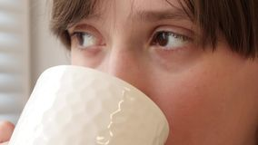 Por mañana una muchacha hermosa bebe té caliente del vidrio blanco y mira hacia fuera la ventana Primer metrajes
