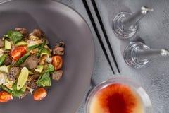 Por met rundvlees en rijst op een mooie plaat met kaarsen en een glas van drank Hawaiiaanse keuken Hoogste mening stock afbeelding