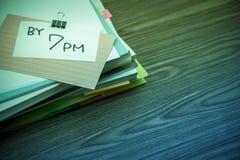 Por 7 PM; A pilha de originais de negócio na mesa Foto de Stock