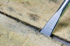 Porada montażu narzędzie wkłada w szczelinę między drewnianymi deskami z bliska Otwiera pudełkowatego concepte zdjęcia stock