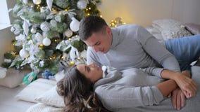 Poranek bożonarodzeniowy, potomstwa dobiera się kłamstwa na łóżku jest w dobrym nastroju na tle xmas drzewo zbiory wideo