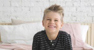 Poratrait of smiling little boy of 5 ages looking at camera sitting in his room.
