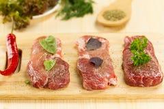 Porc cru frais sur la planche à découper avec des épices photos stock