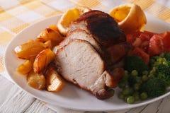 Porc cuit au four avec des pommes de terre, des légumes frais et le pudding de Yorkshire Photos stock