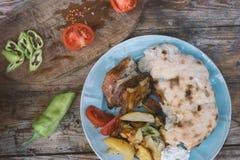 Porc cuit au four avec la pomme de terre et le pain fait maison photos stock