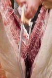 Porc de découpage de boucher dans la moitié Photographie stock